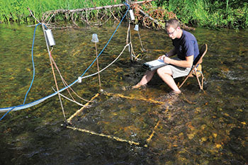 Michigan State University graduate student conducting research with PIT tags and antenae in Ocqueoc River